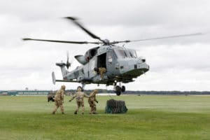 helicopter hovering with three soldiers below